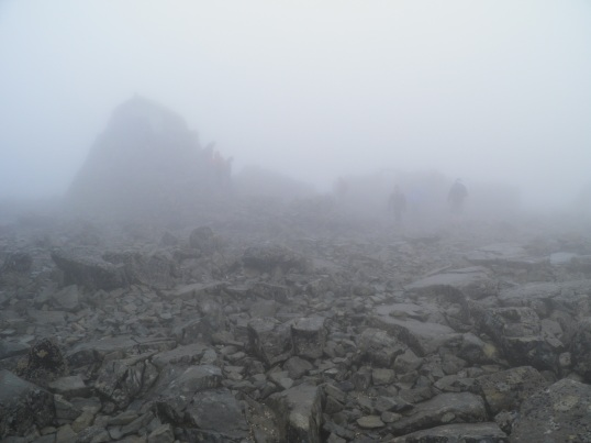 The summit shelter and observatory are just visible through the cloud